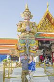 BANGKOK, THAILAND, DECEMBER 26, 2013: Couple of tourists poses in front of a statue in Royal Palace Complex