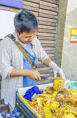 BANGKOK, THAILAND, DECEMBER 26, 2013: Street seller of pineapples peels one of the fruits for buyers