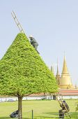 BANGKOK, THAILAND, DECEMBER 26, 2013: Royal Palace and Wat Phra Kaeo Complex - gardeners trim a tree