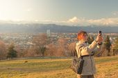 pic of turin  - Lady taking picture with smartphone in backlight with panoramic view of Turin cityscape and the majestic Alps in the background - JPG