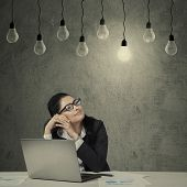 Female Employee With Laptop Looking At Lightbulb