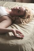 A sad woman taking medication on bed.