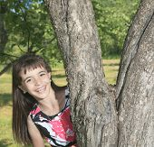 Little girl smile on the side of a tree