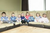 eight little kid sit on the sofa in the living room.
