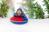 Crazy boy on snow tube in winter fir forest