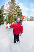 Arabian boy holds shovel and stands in winter