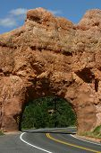 Rocky, arched tunnel greets travelers in southern Utah poster