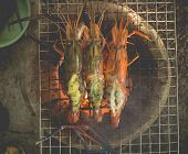 pic of flame-grilled  - Grilled river prawns with butter and herb on flaming grill
