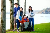 stock photo of biracial  - Disabled little boy in wheelchair surrounded by brother and sisters at lakeside - JPG