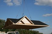 stock photo of trussle  - Crane lifting roof onto prefab home - JPG
