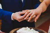 Groom wearing the Diamond ring to bride hand in wedding ceremony. Wedding rings exchange