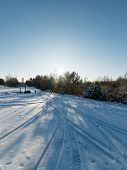 foto of snowy-road  - snowy winter road with tire markings and blue sky - JPG
