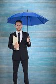 Serious businessman holding a file under umbrella against wooden planks