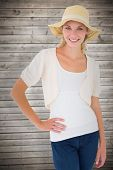 Attractive young blonde smiling at camera in sunhat against wooden planks background