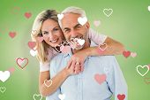 Smiling couple embracing and looking at camera against green vignette