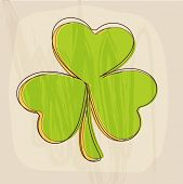 Green shamrock leaf on vintage beige background for Happy St. Patrick's Day celebrations.