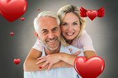 Smiling couple embracing and looking at camera against white background with vignette