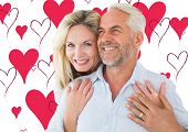 Smiling couple embracing with woman looking at camera against valentines day pattern