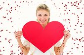 Attractive young blonde showing red heart against red love hearts