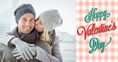 Cute couple in warm clothing hugging man smiling at camera against happy valentines day