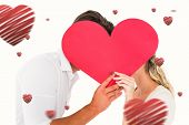 Attractive young couple kissing behind large heart against hearts