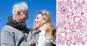 Carefree couple hugging in warm clothing against valentines pattern