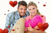 Attractive young couple sitting holding heart cushion against hearts