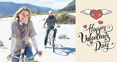 Carefree couple going on a bike ride on the beach against happy valentines day