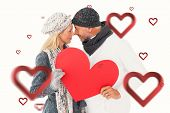 Smiling couple in winter fashion posing with heart shape against hearts