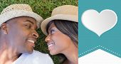 Happy couple lying in garden together against heart label