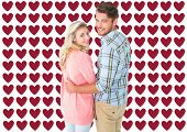 Attractive couple turning and smiling at camera against valentines day pattern