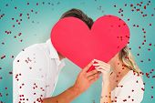 Attractive young couple kissing behind large heart against blue vignette background
