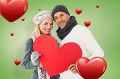 Smiling couple in winter fashion posing with heart shape against green vignette
