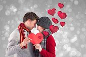 Couple holding a red heart against grey abstract light spot design