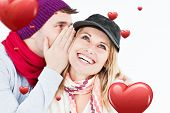 Handsome man with hat telling a secret to his laughing girlfriend against a white background against hearts
