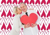 Older affectionate couple holding red heart shape against valentines day pattern