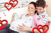 Portrait of a happy pregnant woman holding baby shoes and of her husband on a sofa against hearts