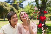Man watching his friend while she is smelling a flower against valentines heart design