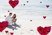 Cute couple drawing a heart in the sand against hearts