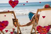 Cute couple holding hands while lying on their deck chairs against happy valentines day