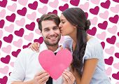Pretty brunette giving boyfriend a kiss and her heart against valentines day pattern