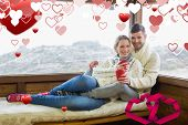 Couple in winter wear with coffee cups against cabin window against linking hearts