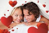 Couple under a duvet with a knowing smile against love heart pattern