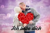 Happy mature couple in winter clothes holding red heart against pink and purple girly design
