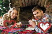 Smiling couple with tea cups in front of lit fireplace against i love you