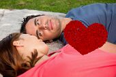Man looking into his friends eyes while lying on a quilt against red love hearts