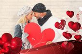 Smiling couple in winter fashion posing with heart shape against white wall