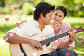 Man playing the guitar while his friend watches him against valentines heart design