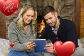 Couple using tablet PC in front of lit fireplace against cute valentines message