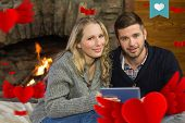 Couple using tablet PC in front of lit fireplace against heart label